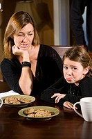 Mother and daughter sitting at dining room table with cookies