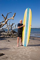 Mature man in wetsuit on beach with surfboard