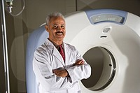 African American radiologist next to CT scanner