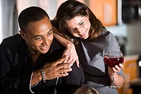 Multi_ethnic couple relaxing with glass of wine at home