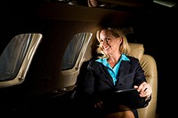 Businesswoman traveling in corporate jet