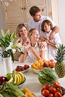 Young family in dining room eating fresh fruits and vegetables