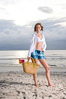 Young woman standing on beach with handbag and flowers