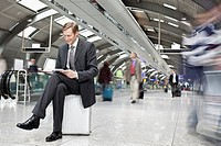 Businessman reading in airport terminal