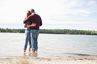 Couple wading in lake hugging