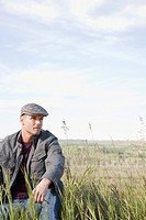 Man sitting in marshy meadow