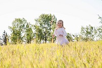 Little girl running through tall grass in meadow