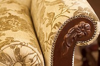 Hard carved armrest on upholstered sofa