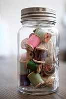 Mason jar filled with spools of thread