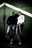 Two young women leaning against an old steel door, youth, cool