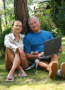Couple with laptop in the garden