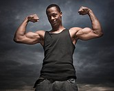 African man flexing arms, storm clouds in distance