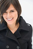 Hispanic woman in winter coat smiling