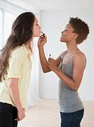 Woman putting lip gloss on friend