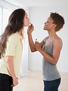 Woman putting lip gloss on friend