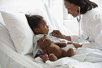Doctor examining girl in hospital bed