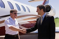 Businessman and pilot shaking hands outside private jet