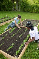 A girl weeds a garden, aided by a counselor, in a program called Growing Healthy Kids for children ages 5-11, as part of the Earthworks Urban Garden, ...