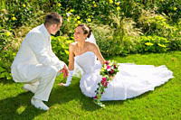 Bride lying on the ground looking at her groom smiling in a park