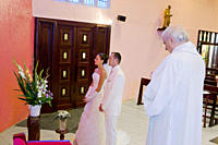 Bride and groom praying in church with the priest shortly after the ceremony