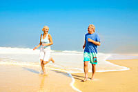 Senior couple jogging together on a shore on bright sunny day