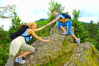 Two women hiking and helping each other to climb on a rock