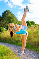 Two women working out outdoors and giving each other a piggyback ride