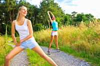 Two sporty women working out outdoors and doing stretching exercises together