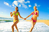 Two young women dressed in bikinis jogging along the coastal line and holding their hands
