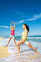 Two women working out the beach and having fun while doing stretching exercises together