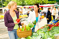 Two young women buying healthy fruits and vegetables on the market together