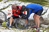 Mountain bike riders repairing a flat front tyre