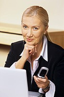 Businesswoman holding a mobile sitting in front of a personal computer.