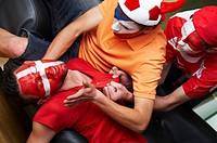 Unconscious sport fan with two other fans helping him.