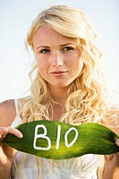 Young woman holding a leaf with BIO lettering