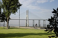 Cyclists in front of the Vasco da Gama bridge over the Rio Tejo river in the Parque das Nacoes park, site of the Expo 98, Lisbon, Portugal, Europe