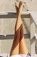 Young woman's legs lying outdoors, sunbathing