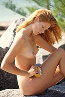 Naked young woman massaging her thigh, sitting on a rock, seaside