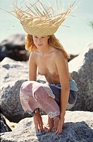 Young woman crouching on a rock, topless, sunhat