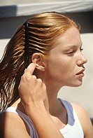Young woman combing her hair, outdoors