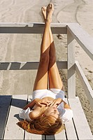 Young woman lying outdoors, sunbathing (thumbnail)