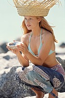 Young woman holding a shell full of water, outdoors