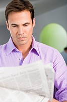 Close_up of a man reading a newspaper