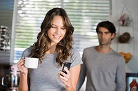 Woman text messaging with a man standing in the background