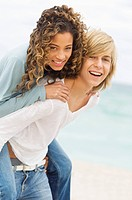 Girl riding piggyback on a teenage boy on the beach (thumbnail)