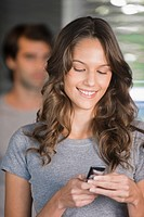 Woman text messaging on a mobile phone (thumbnail)