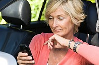 Woman sitting in a car and text messaging
