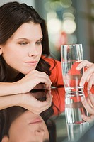 Woman looking at a glass of water (thumbnail)