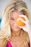 Close_up of a woman holding an orange in front of her eye