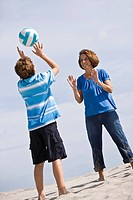 Woman with her grandson playing beach volleyball